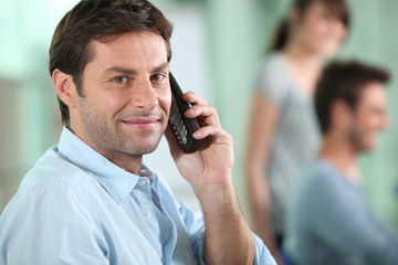 Businessman holding mobile phone with colleagues