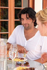 a man uncorking a wine bottle and a woman during the dinner