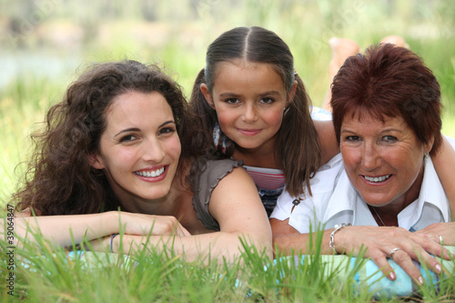 Grandmother, mother and daughter lying in the grass