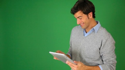 Young man standing on green background wth tablet