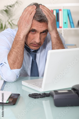 Stressed man using laptop