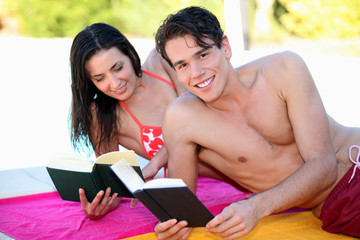 Couple reading books on the beach