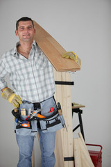 Carpenter carrying a wooden plank