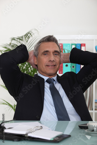 businessman with his hands behind his head