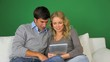 Couple using electronic tablet on green background