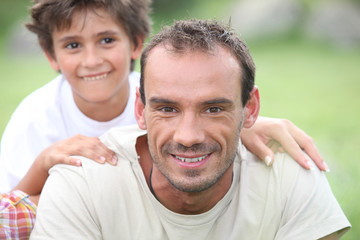Portrait of happy man with little boy outdoors,