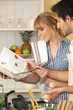 Young couple using a cookbook
