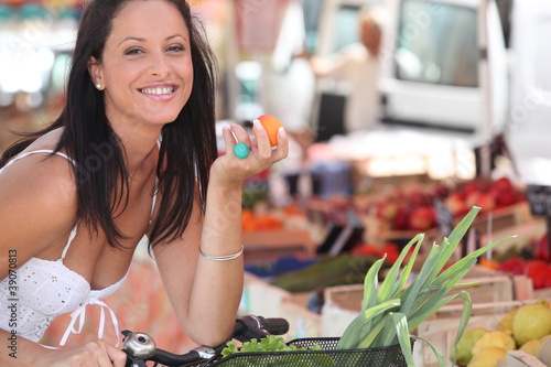 Brunette buying fruit and vegetables at local market