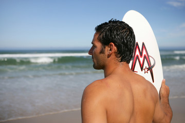 Man with a surfboard looking at the ocean