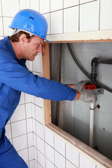 Plumber tightening a pipe