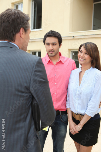Estate agent meeting couple for viewing