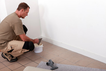 handyman laying fitted carpet