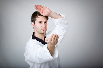 Young man practicing martial arts over gray background