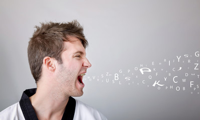 Young martial arts man shouting over gray background
