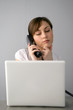 Woman looking at her laptop while talking on the phone