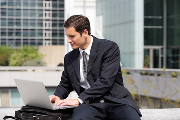 Businessman sat using laptop in the city