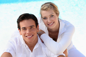 Couple sat by swimming pool