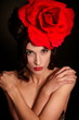 fashion woman with bright makeup lips with big red rose on head