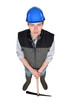 Young construction worker stood with pick-ax