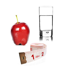 Apple glass of water and tape measure on white background