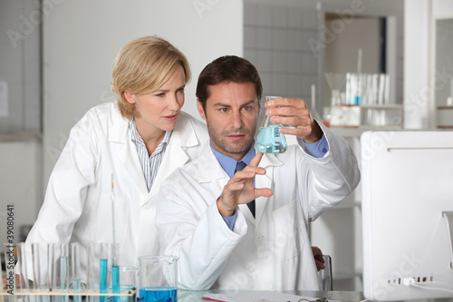 Laboratory team examining blue liquid