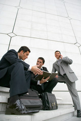 Businessmen sitting outside a city building