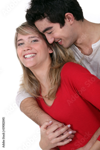 Young couple hugging in studio