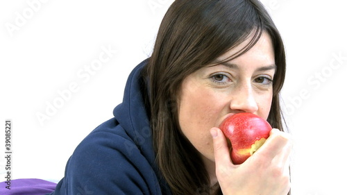 young woman eating red apple smiling