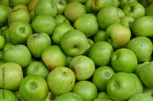close up of green apples on market stand