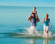 Happy summer vacation - family playing in the sea