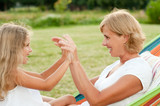 Happy childhood - Mother and daughter playing in hammock poster