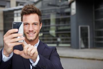 Mann fotografiert mit Smartphone