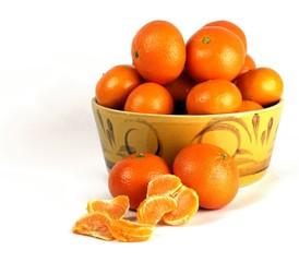 Oranges tumbling from an orange ceramic bowl