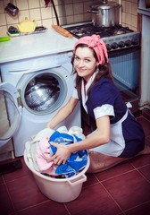 young housewife with washing machine and towels.