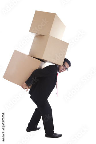 Businessman carrying heavy boxes