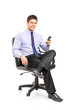 Young businessman sitting on a chair and holding a mobile phone