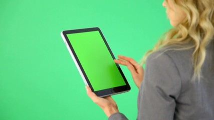 Businesswoman on green background with digital tablet