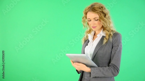 Businesswoman standing on green background with digital tablet