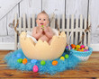 adorable baby sitting in giant easter egg