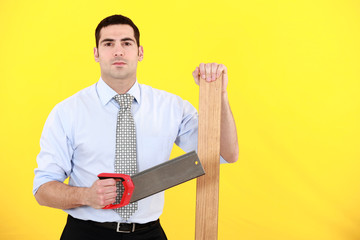 Professional holding a saw and a plank of wood