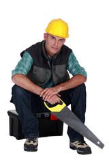 Workers sitting on toolbox with saw in hand