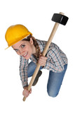 Woman crouching with hammer
