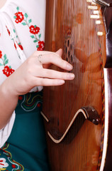 Closeup view on girl hand playing by bandura