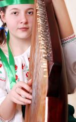 Closeup portrait tennage girl playing by bandura