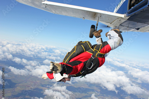 Fototapeta Skydiver jumps from an airplane