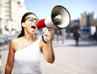 portrait of a middle aged woman shouting with megaphone at a cro