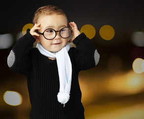 portrait of funny kid holding his glasses  at city by night