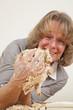 lachende Frau beim Backen macht Quatsch mit Teig
