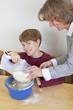 Junge macht Faxen beim Backen mit seiner Mutter