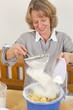 Backen mit Schwung - Hausfrau siebt Mehl in Schüssel